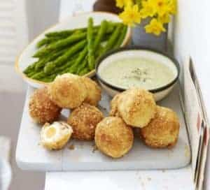 A serving of scotch quail eggs with asparagus and mayonnaise