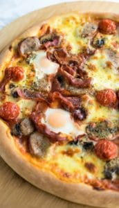 A freshly baked Florentine Quail Eggs Pizza on a wooden board