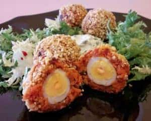 Serving of spicy scotch quail eggs with pesto-yogurt dip and salad