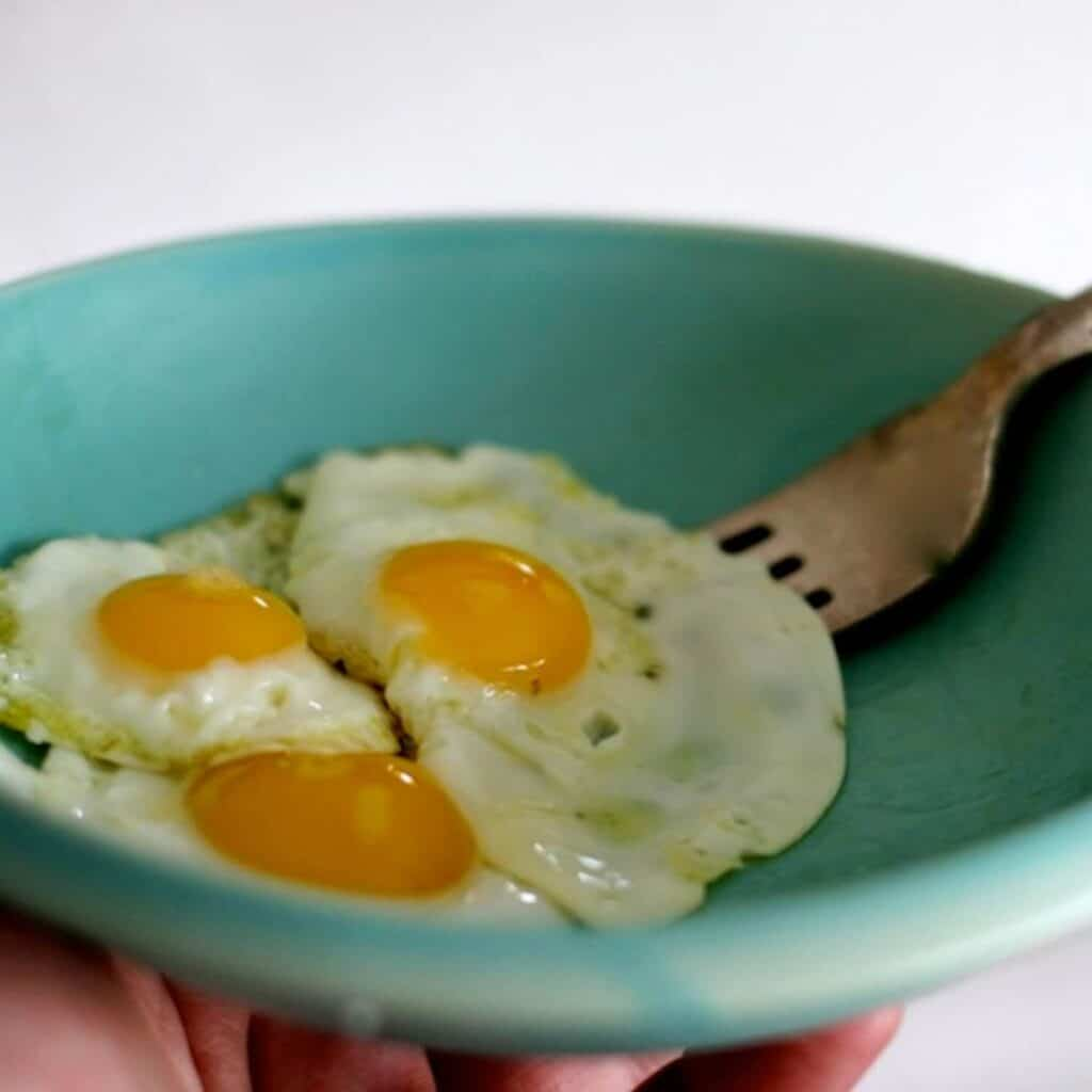 3 fried quail eggs in a light blue bowl with fork